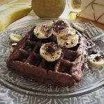 Whole-Wheat Cocoa Banana Waffles served with banana and chocolate