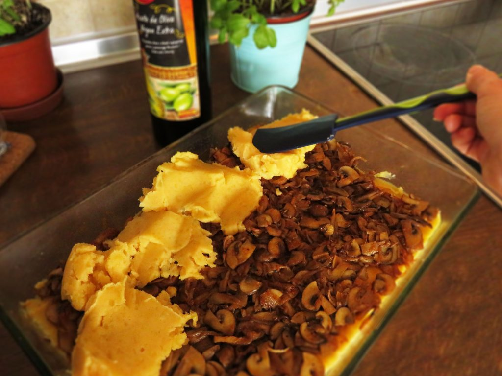 Layering the ingredients together in a baking dish for Mushroom Shepherd's Pie