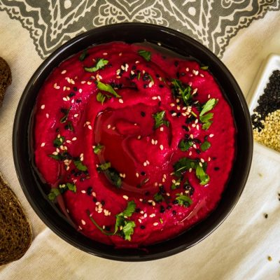 Creamy Beetroot Hummus served in a bowl with sesame seeds and chopped parsley